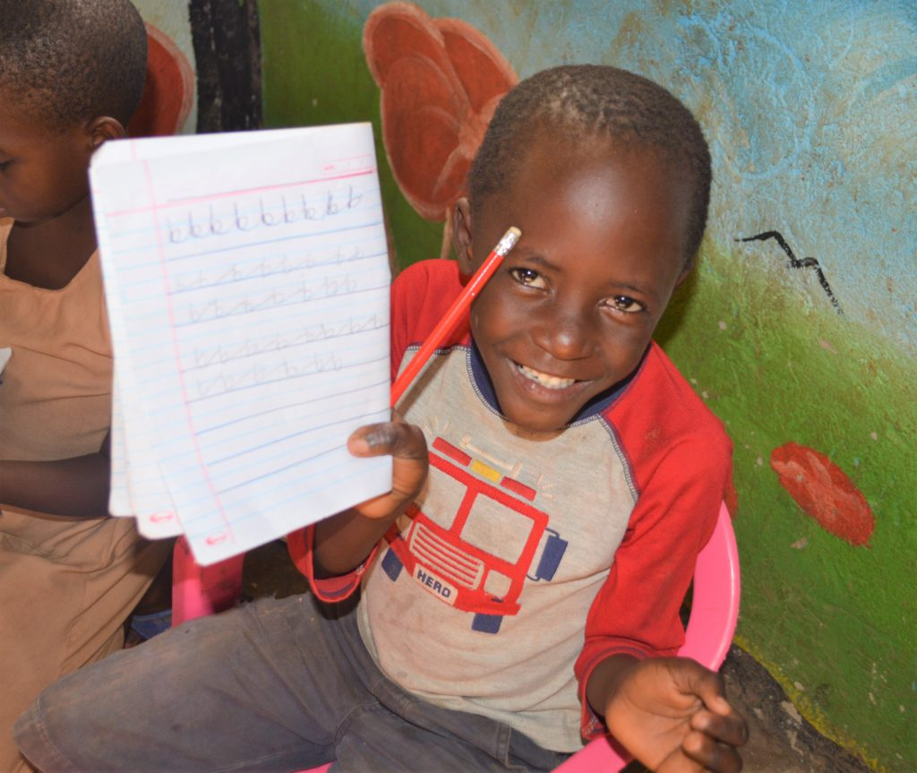Smiling school aged boy with his school book and pen