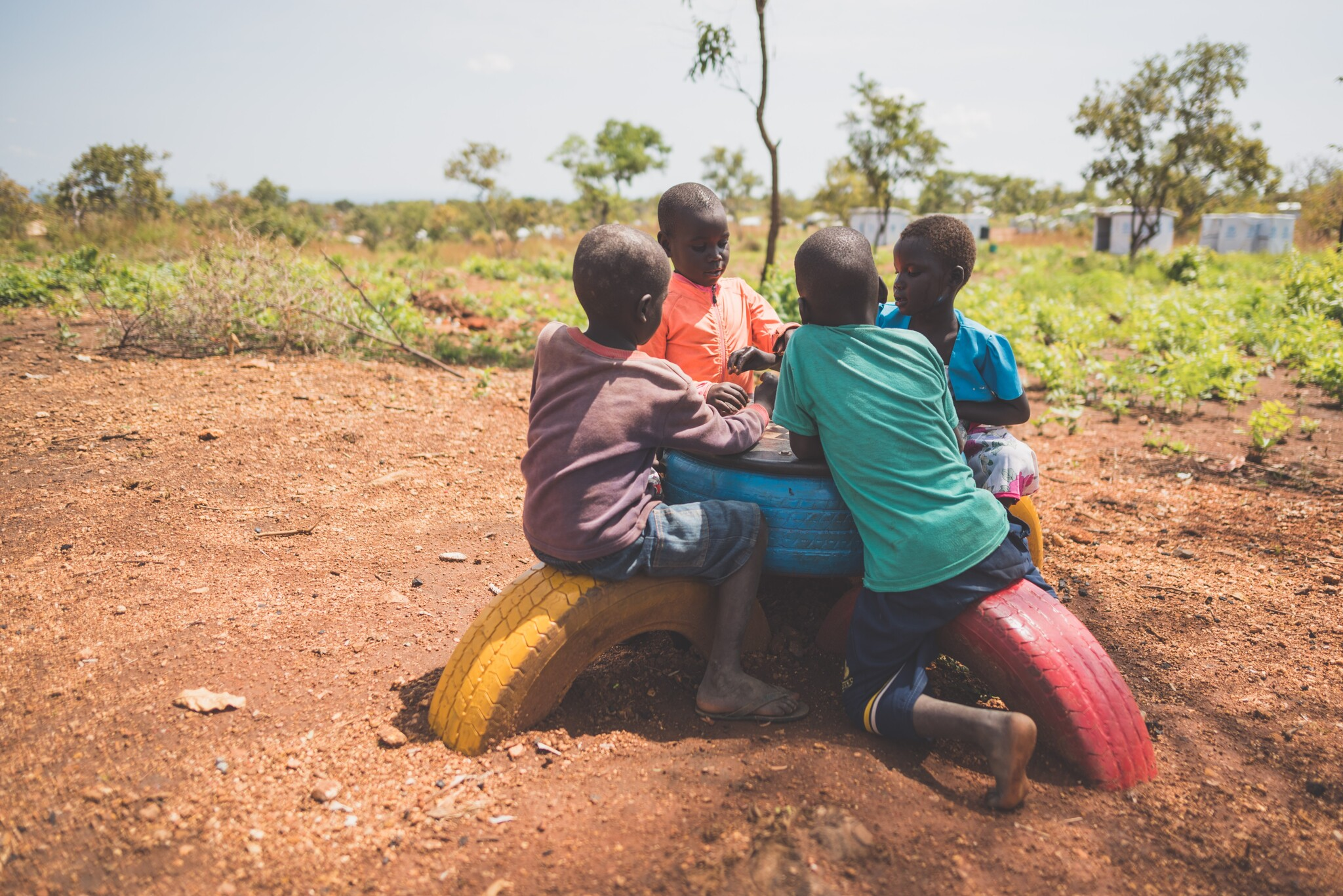 Four young boys sit around a bench made of painted car tyres and play a game together.
