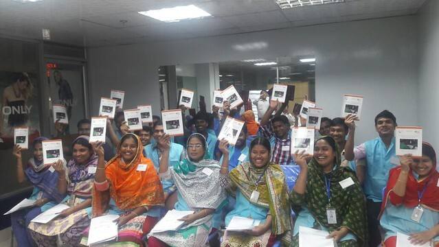 A smiling group of adults sit in a classroom