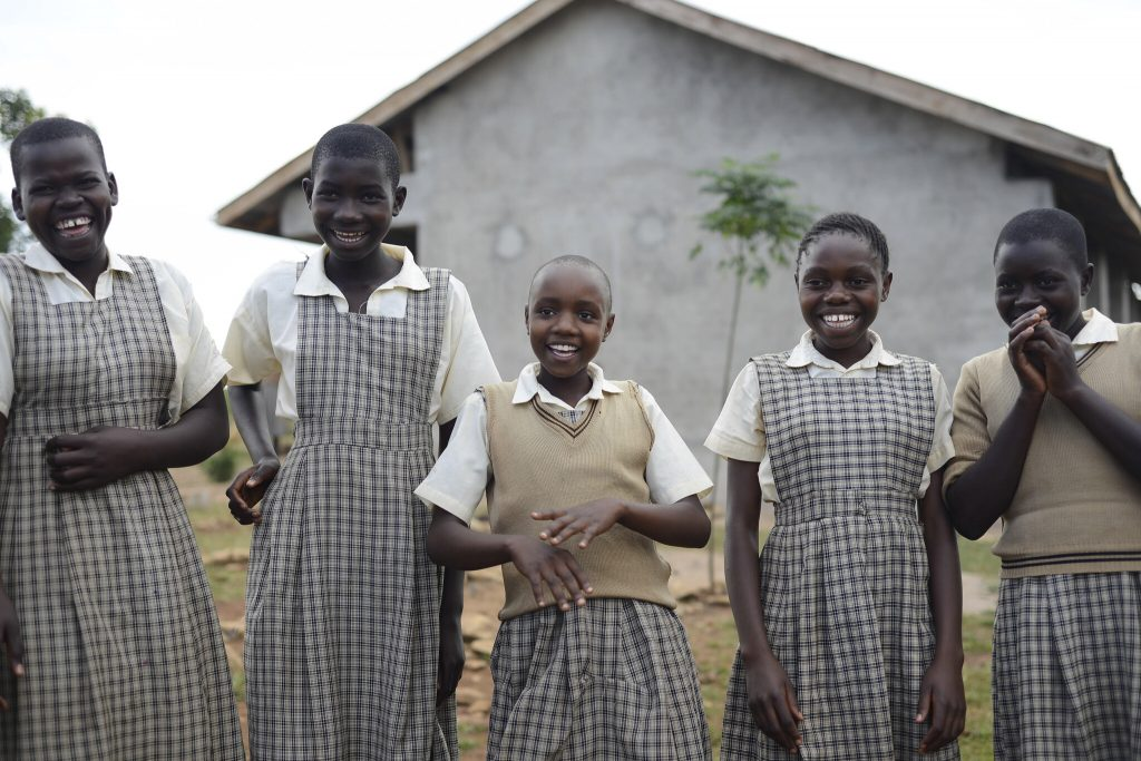 Five smiling school girls outside a building